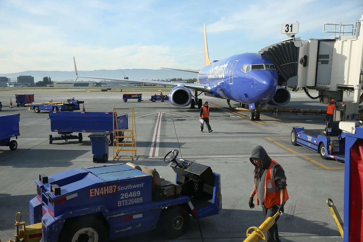 Airport personnel work on the tarmac outside the temporary Terminal C and next to the permanent gates for the terminal that will he built in the future at Norman Y. Mineta San Jose International Airport on Tuesday, January 7, 2020 in San Jose, Calif.
