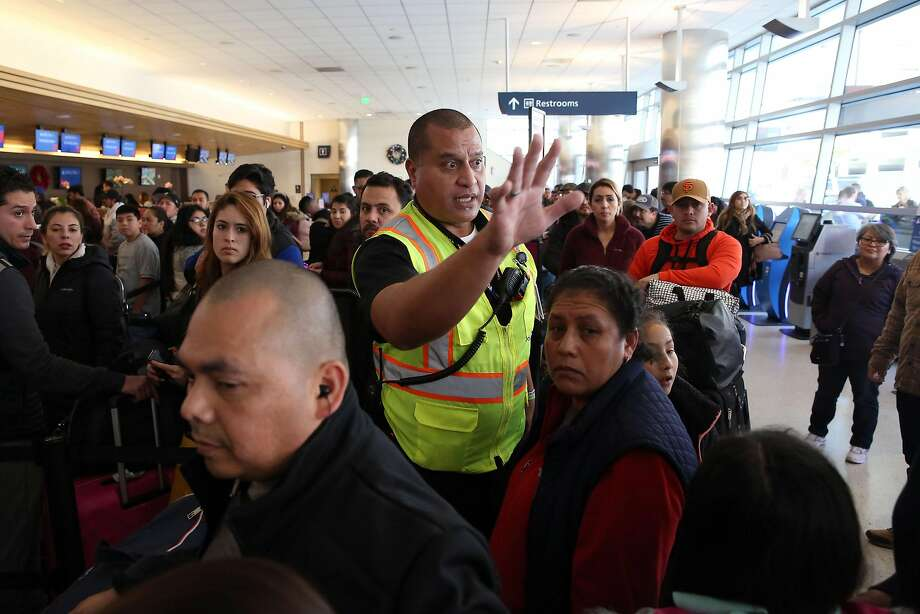 Michael Aliki, with airport operations, directs passengers at Mineta San Jose International Airport, which is planning to expand to meet demand. Photo: Lea Suzuki / The Chronicle