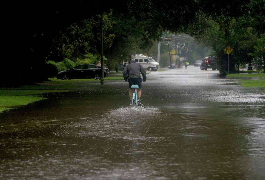A man bicycles down 23rd Street, which was one of the Beaumont regions hit by damaging flooding. Boaters and other emergency personnel were conducting rescue missions to those in need throughout the morning and afternoon. Photo taken Thursday, September 19, 2019 Kim Brent/The Enterprise Photo: Kim Brent / The Enterprise / BEN