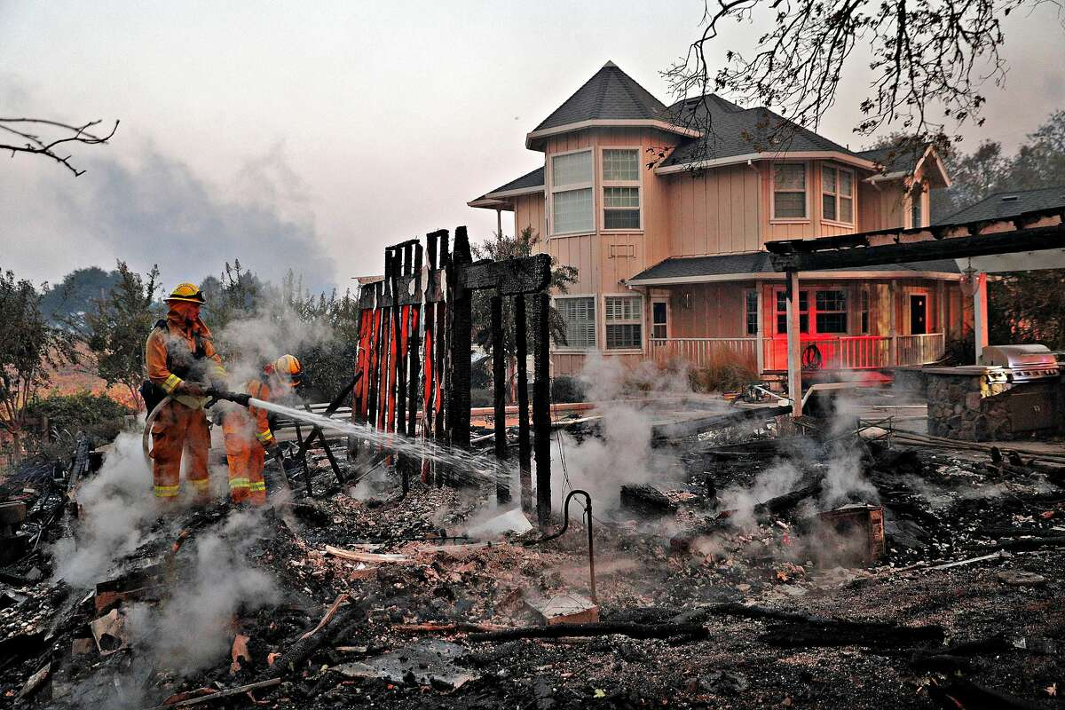 Firefighters extinguish hot spots in an out builiding that burned next to a house that was spared on Chalk Hill Road as the Kincade Fire burns outside Healdsburg, Calif., on Sunday, October 27, 2019.