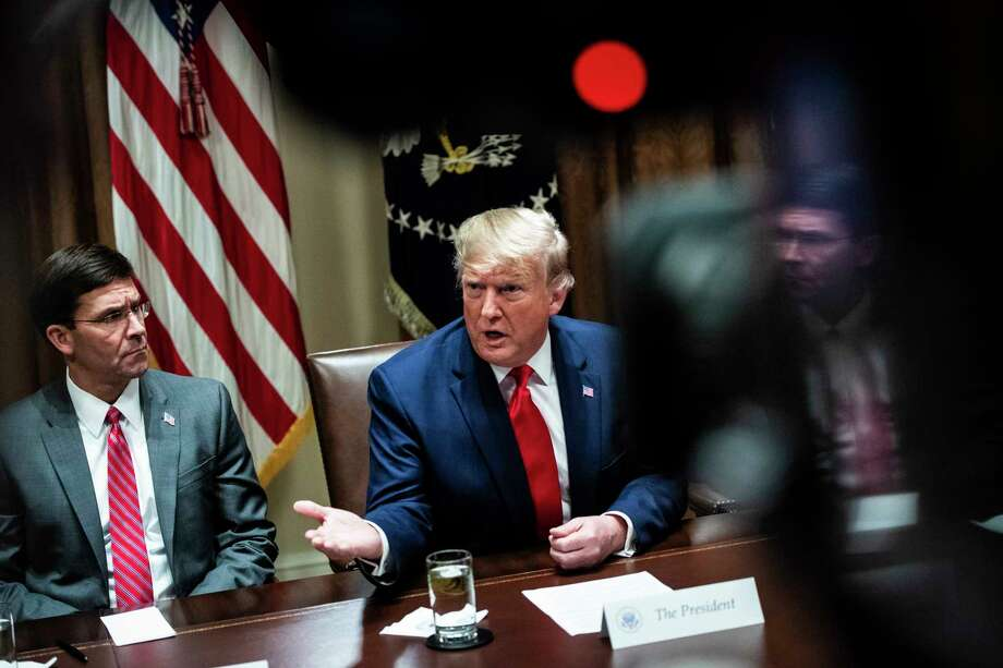 President Donald Trump, flanked by Secretary of Defense Mark Esper, speaks during a meeting with senior military leaders in October 2019. Photo: Washington Post Photo By Jabin Botsford / The Washington Post