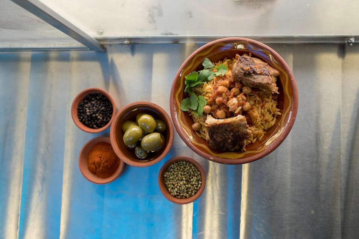 Tli tli bdjedj, a chicken tomato stew served over orzo, at their Algerian food truck, Kayma on December 22, 2019 on Treasure Island in San Francisco, California.