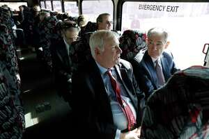 Federal Reserve Bank of Boston President Eric Rosengren, center front, and Federal Reserve Board Chairman Jerome Powell, right, participate in a bus tour of East Hartford on Nov. 25. They toured a neighborhood and met with residents as part of the Boston Fed's Small Cities Challenge. On Monday, Rosengren, in Hartford, said the economy is entering a 'soft landing.'