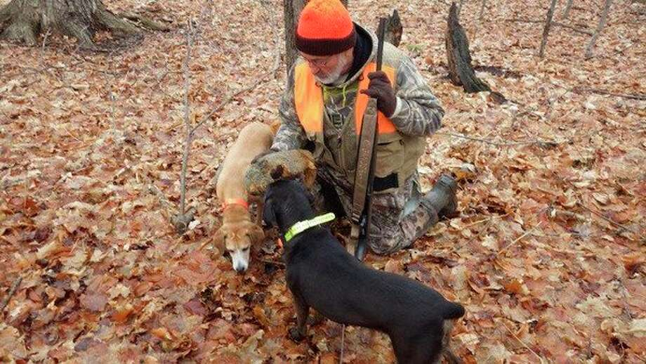 "Bob Walker of Kingston thanks the Mountain Curs on a job well done treeing a squirrel. The black dog is Tom Lounsbury's ""Jilly."" (Tom Lounsbury/Hearst Michigan)"