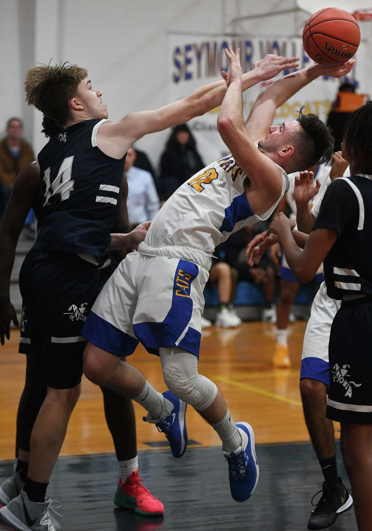 Ansonia's Noah Wagnblas, left, looks to block a shot in the lane by Seymour's Matthew Oczkowski during the first half of their boys basketball game on Monday at Seymour High School.