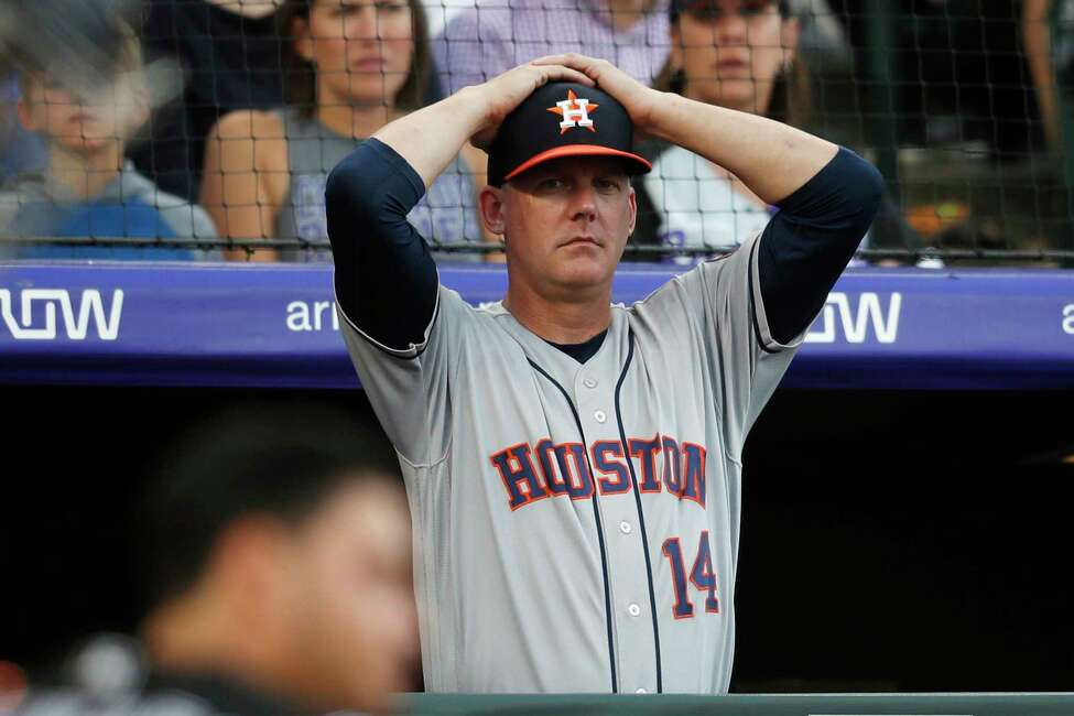 FILE - In this July 2, 2019, file photo, Houston Astros manager AJ Hinch reacts during a baseball game against the Colorado Rockies, in Denver. Houston manager AJ Hinch and general manager Jeff Luhnow were suspended for the entire season Monday, Jan. 13, 2020, and the team was fined $5 million for sign-stealing by the team in 2017 and 2018 season. Commissioner Rob Manfred announced the discipline and strongly hinted that current Boston manager Alex Cora a€?