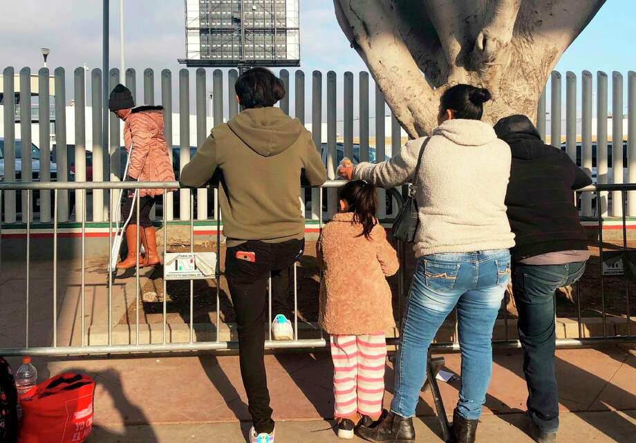 En esta fotografía del miércoles 8 de enero de 2020, unas personas que buscan solicitar asilo en Estados Unidos esperan en un puente fronterizo de Tijuana, México. Photo: Elliot Spagat /Associated Press / Copyright 2020 The Associated Press. All rights reserved.