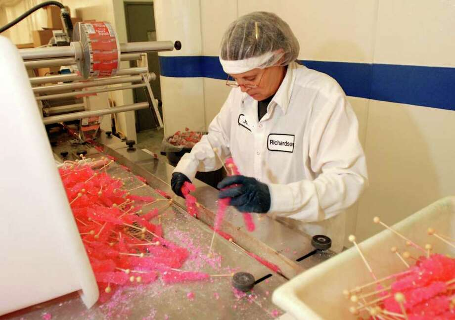 Machine operator Jody Gloskey prepares cherry rock candy for the packing machine on Thursday at Richardson Brands Co. in Canajoharie. Just the packing of this product occurs at this facility, but the rock candy will be manufactured here in September when the business moves here from Branford, Conn. (Cindy Schultz / Times Union) Photo: Cindy Schultz