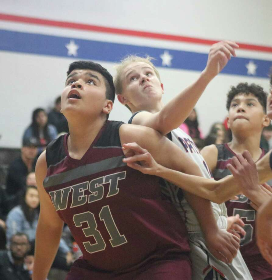 Pearland West's Sean Garza attempts to keep a Bondy player away from the ball as the two fight for a rebound after a foul shot during Saturday's contest. Photo: Robert Avery