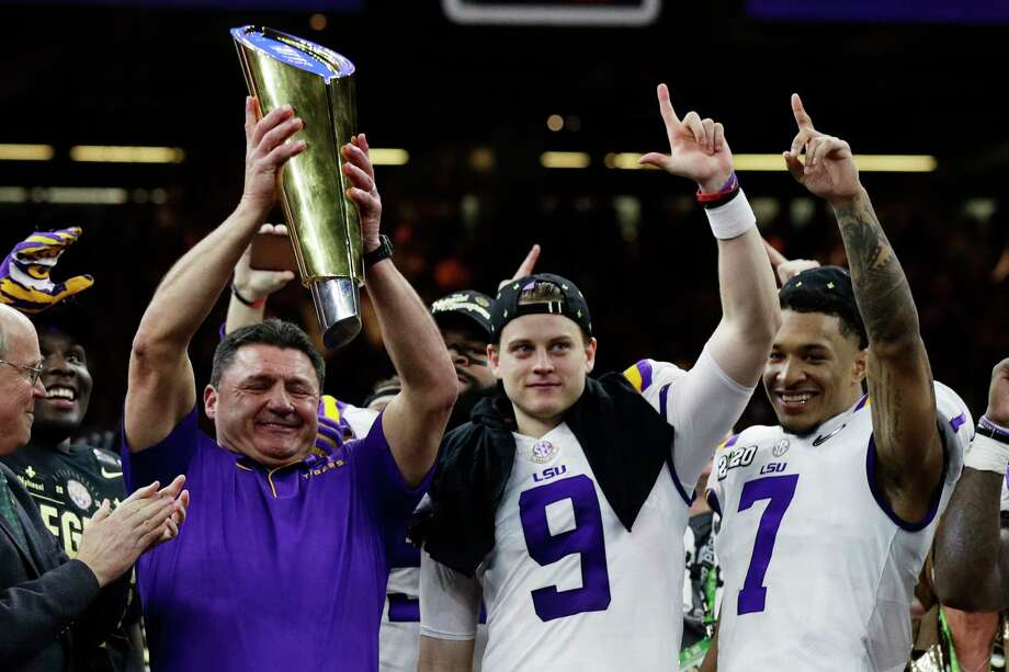 LSU head coach Ed Orgeron holds the trophy beside quarterback Joe Burrow, center, and safety Grant Delpit after a NCAA College Football Playoff national championship game against Clemson, Monday, Jan. 13, 2020, in New Orleans. LSU won 42-25. (AP Photo/Sue Ogrocki) Photo: Sue Ogrocki, Associated Press / Copyright 2020 The Associated Press. All rights reserved
