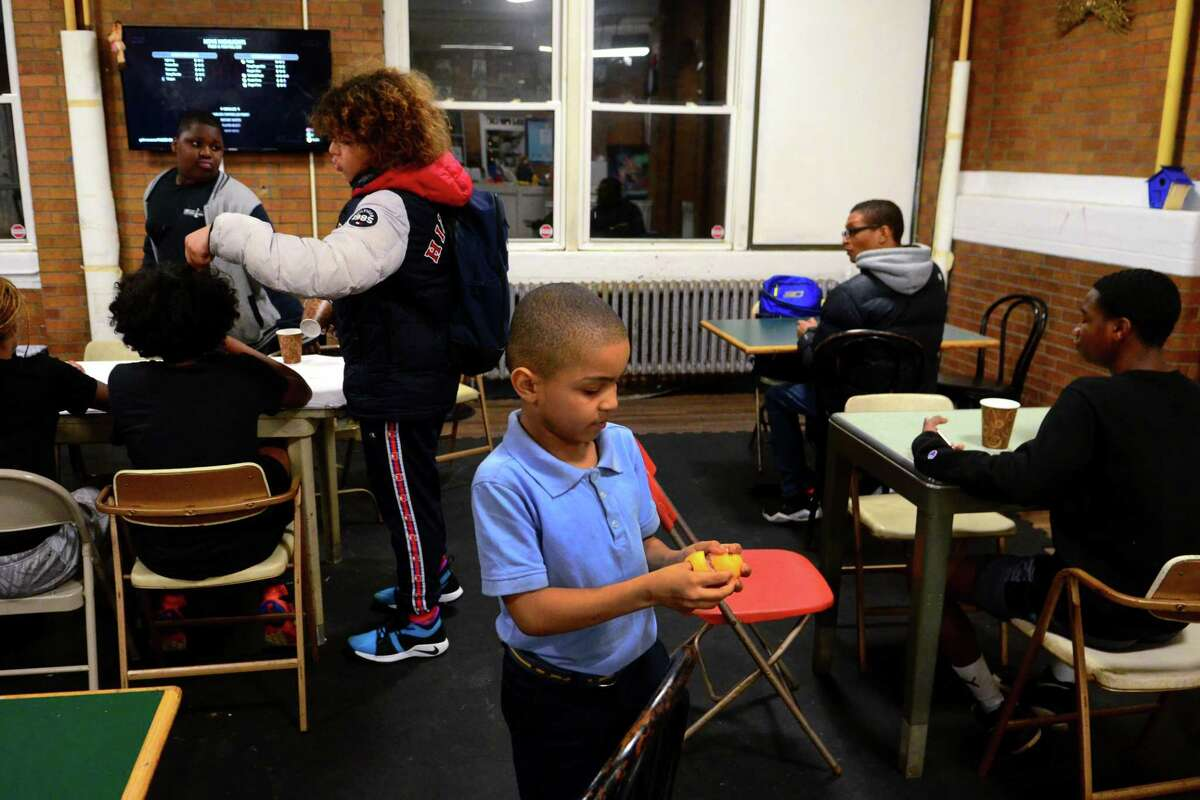 Orcutt Boys & Girls Club member Jayson, 11, enjoys an orange as part of a hot meal held each weekday for the kids at the facility on Park Street in Bridgeport, Conn., on Jan. 2, 2020. The meal train was spearheaded by Orange mom Christina Skrieh who brings her 12-year-old son Sami to the club for basketball.