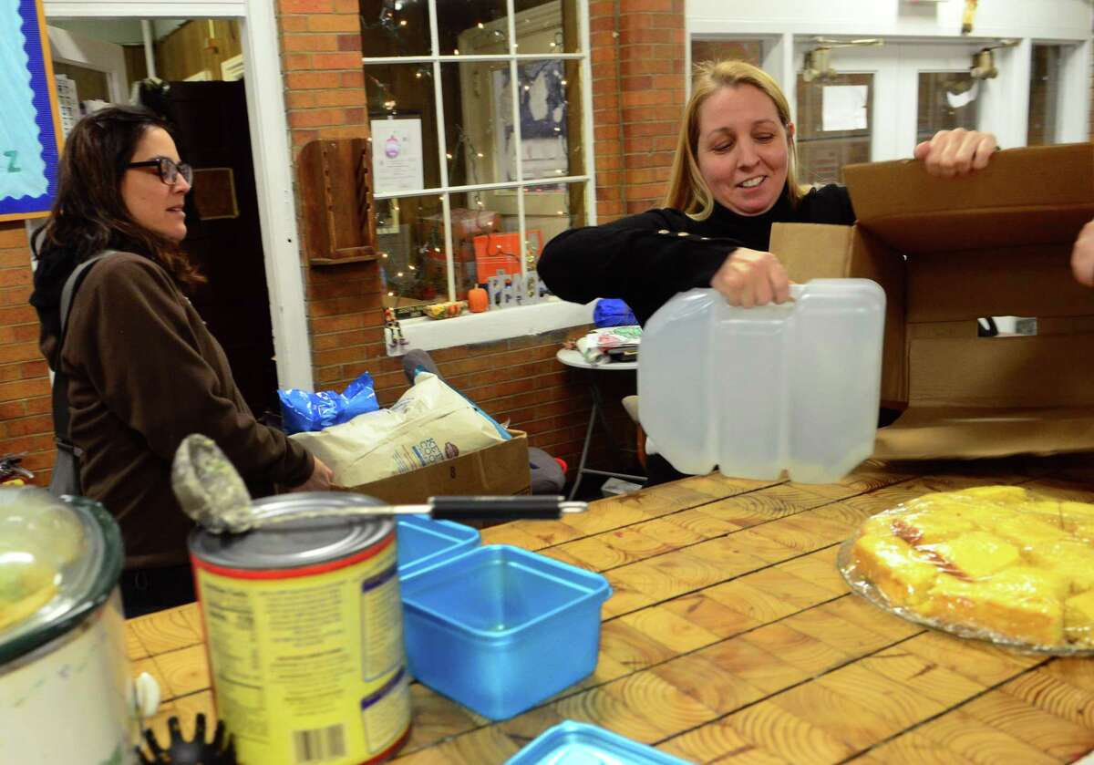 Christina Skrieh of Orange, right, works to set up a meal train held each weekday to feed the kids at the Orcutt Boys & Girls Club on Park Street in Bridgeport. At left is friend Erica Somerville of Trumbull, who came along to help out.