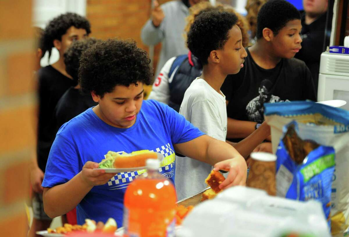 Orcutt Boys & Girls Club member Nate, 14, gets a hot meal as part of meal train at the facility on Park Street in Bridgeport.