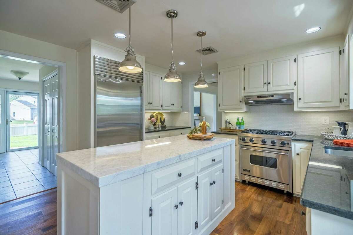 The high-end renovated eat-in kitchen has a center island topped with marble, granite counters, and high-end appliances.