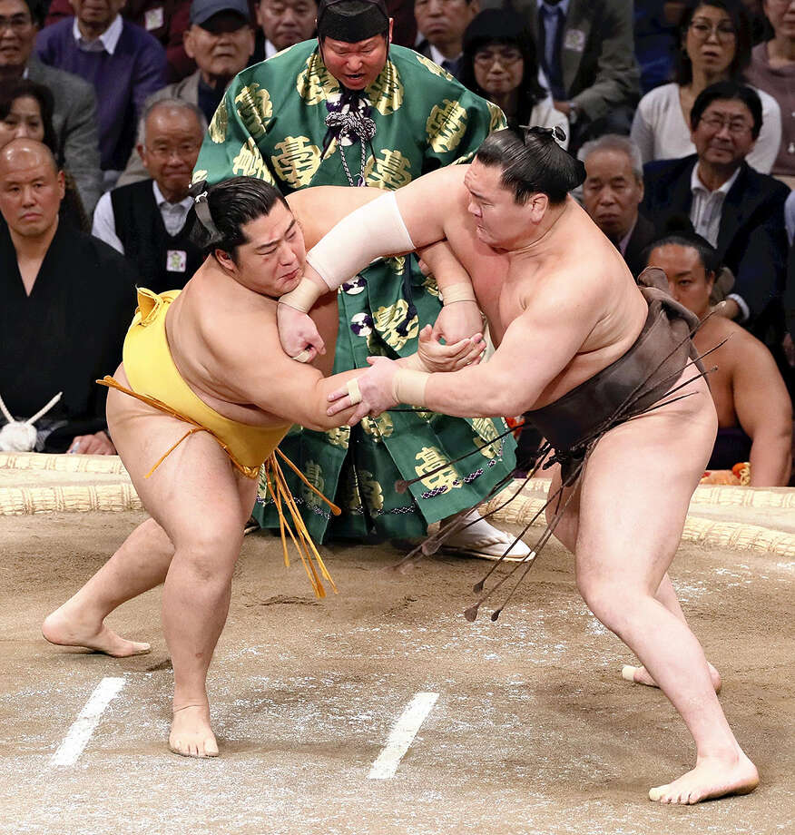 Yokozuna Hakuho, right, charges at komusubi Endo with a kachiage move on the 12th day of the Kyushu Grand Tournament on Nov. 21, 2019. Photo: Japan News-Yomiuri Photo / Japan News-Yomiuri