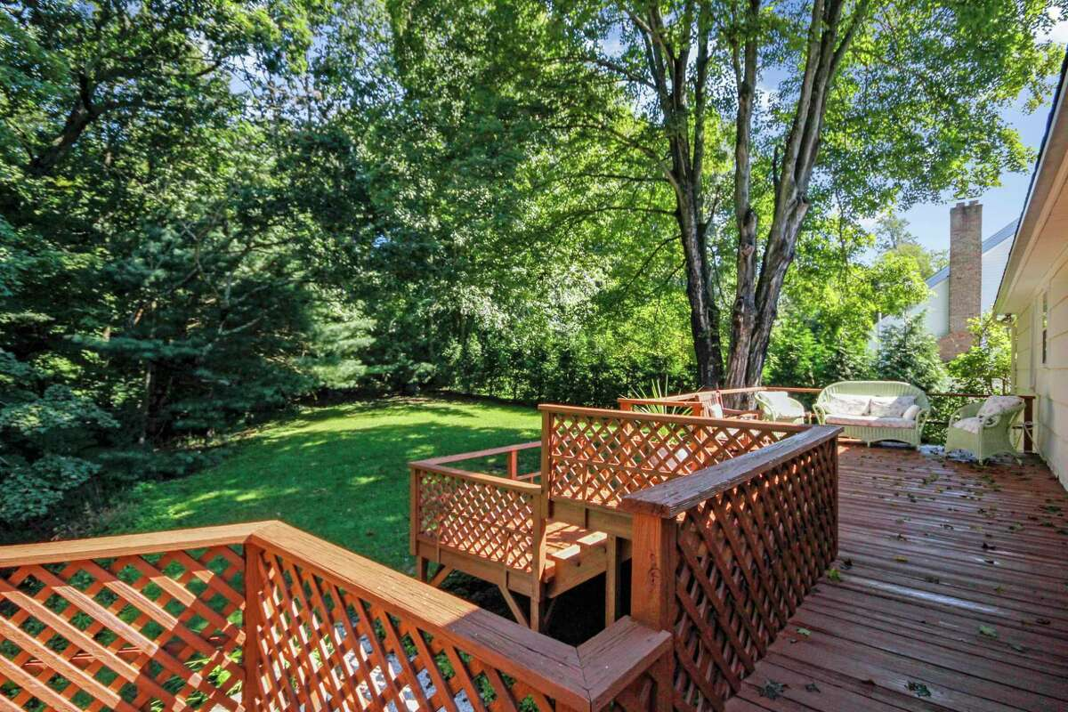 The large raised wood deck has multiple tiers and looks over the private back yard and Lee Pond.