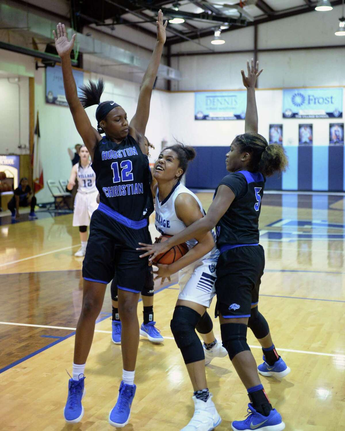 Jada Malone (23) of Village attempts to drive past Autumn Nicholas (5) and Amani Bartlett (12) of Houston Christian during the first quarter of a varsity girls basketball game between The Village Vikings and the Houston Christian Mustangs on Friday January 5, 2018 at The Village School, Houston, TX.