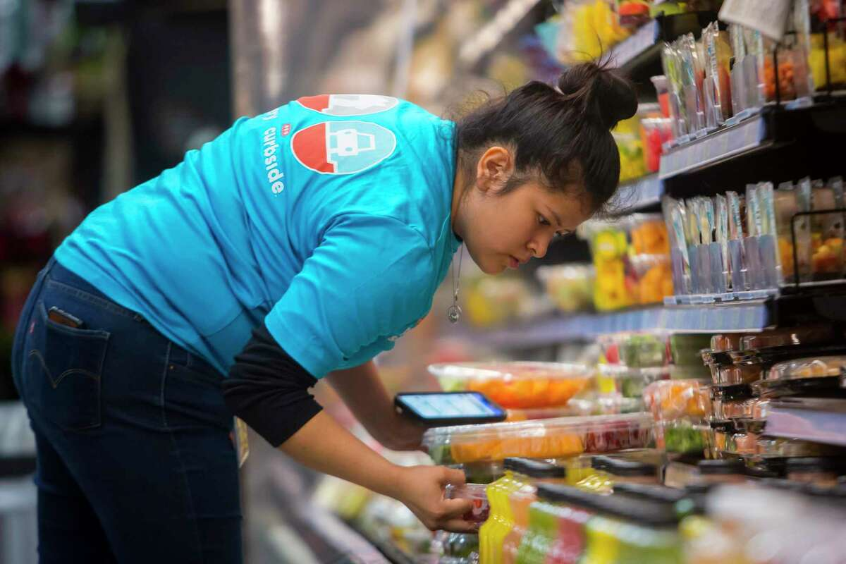 H-E-B personal shopper Brenda Flores checks items as she gathers cold food products for a curbside order inside the Buffalo Heights H-E-B store on Tuesday, Dec. 10, 2019.