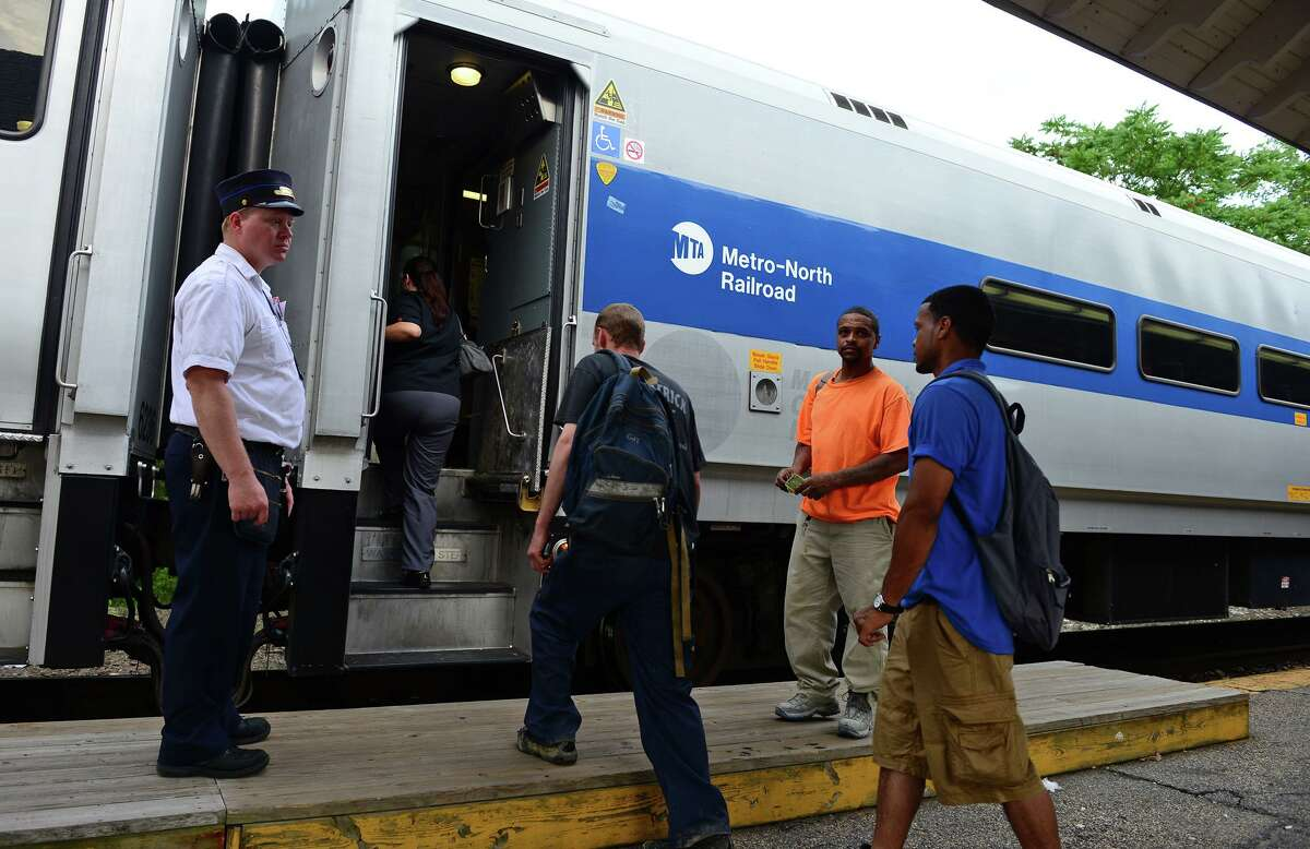 Commuters enter the Waterbury bound train at the Metro-North Derby train station in Derby, Conn. on Wednesday July 9, 2014.