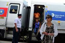 Commuters exit the Waterbury bound train at the Metro-North Derby train station in Derby, Conn. on Wednesday July 9, 2014.