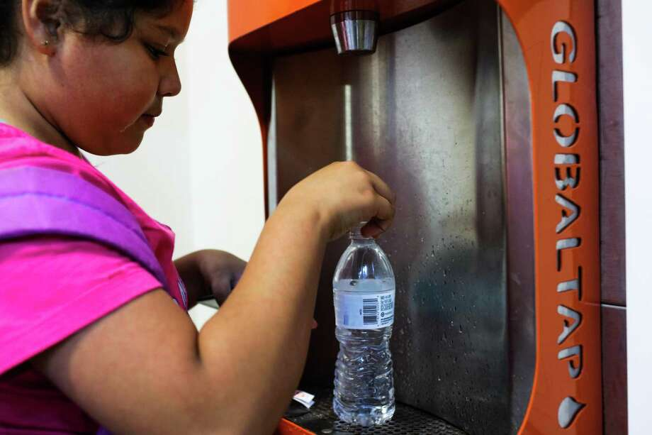 A woman up her water bottle at a refill station. Photo: Hearst Connecticut Media File Photo / ONLINE_YES