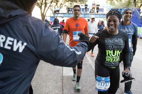 Petra Montgomery is greeted at the finish line by volunteer Giovanni Anderson during the Chevron Houston Marathon on Sunday, Jan. 20, 2019, in Houston.
