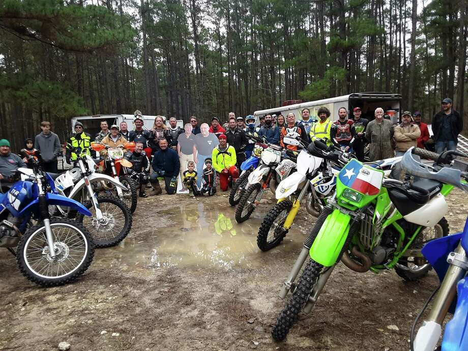 A large group of motorized dirt bike riders are pictured with cardboard cutouts of Mark Tracy and Larry Faulk. They passed away recently and the ashes of the two friends, Mark Tracy and Larry Faulk, were carried by their companions on the West Side Trail last year, and on the reopened East Trail this year. Photo: Courtesy Photo