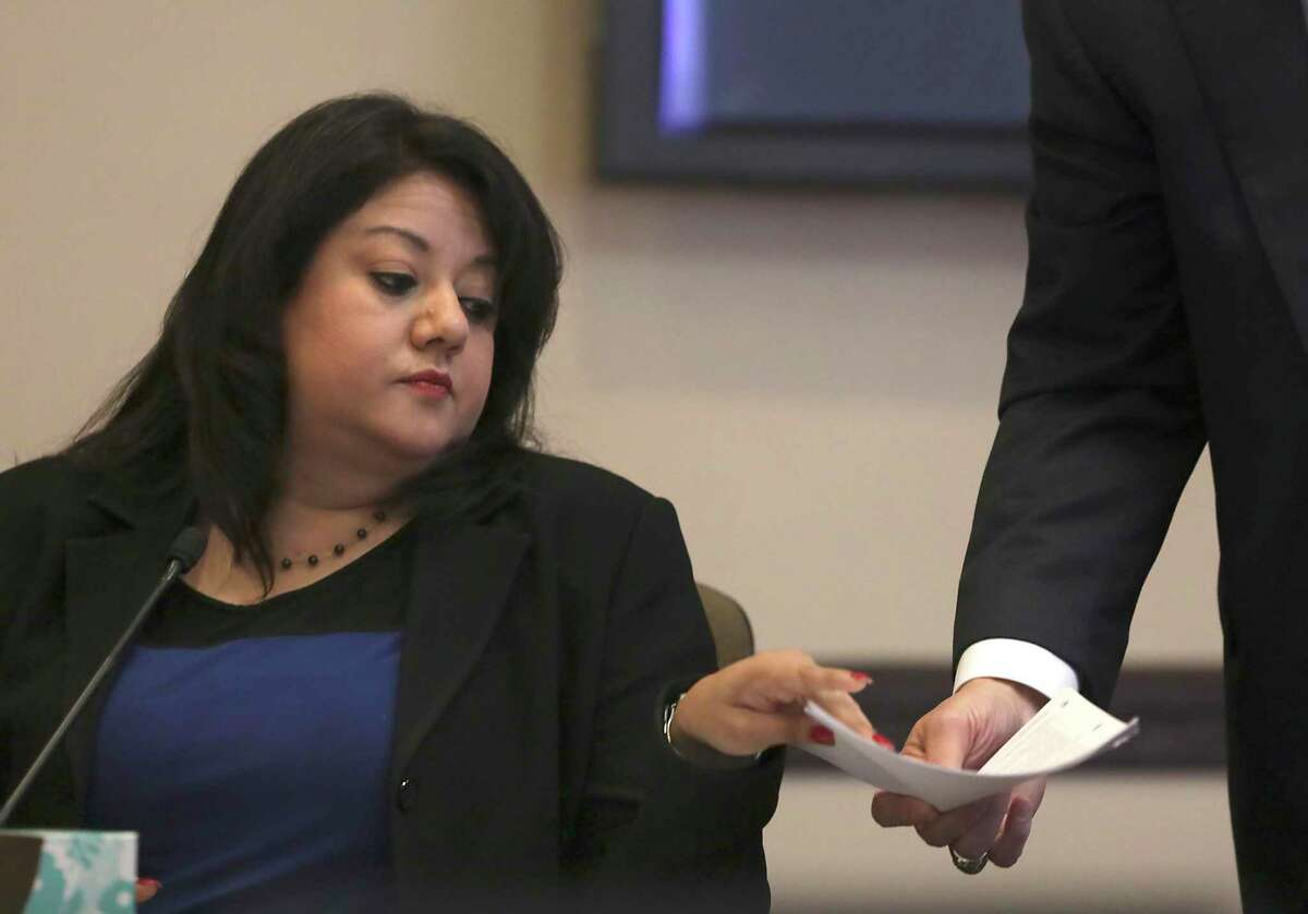 Monica Alcantara, Bexar County Democratic Party chair, takes a document to read during a court hearing regarding a civil lawsuit in April 2019.