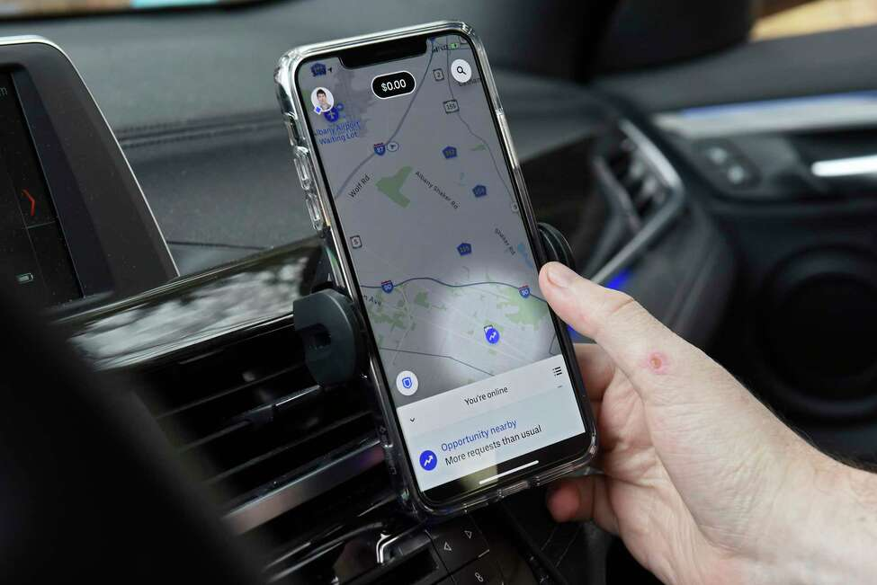 Kraig Roche, a driver for Uber and Lyft, checks for potential customers from his smartphone in his car on Tuesday, Jan. 14, 2020 in Albany, N.Y. Roche is the founder of a private Facebook group consisting of ride-share drivers from across the Capital Region. (Lori Van Buren/Times Union)