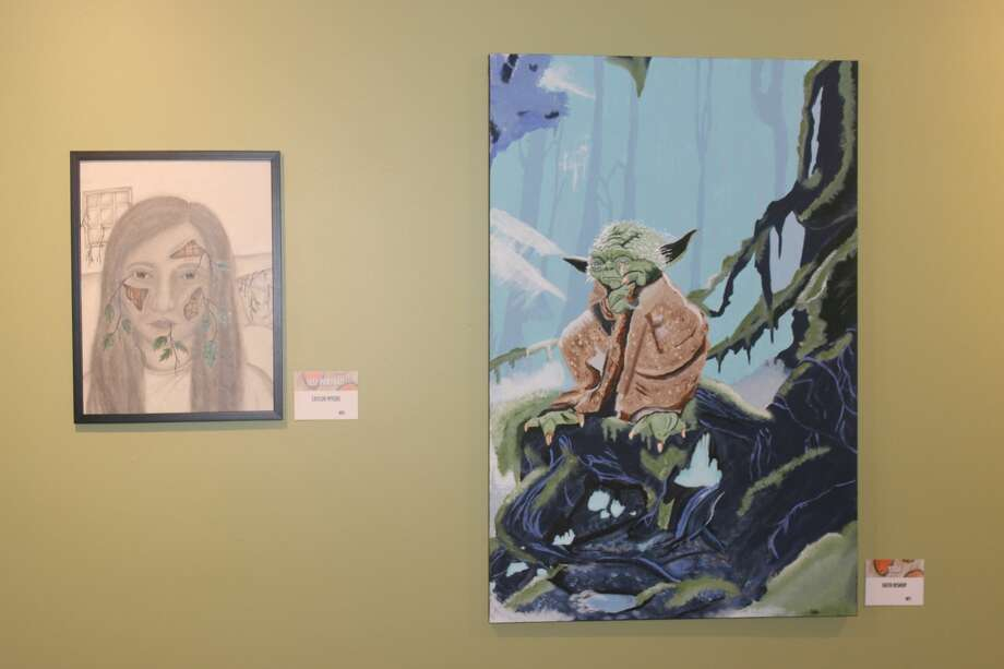 A self-portrait by Taylor Myers (left) and a painting of Yoda by Faith Bishop (right) are displayed. Photo: Robert Myers