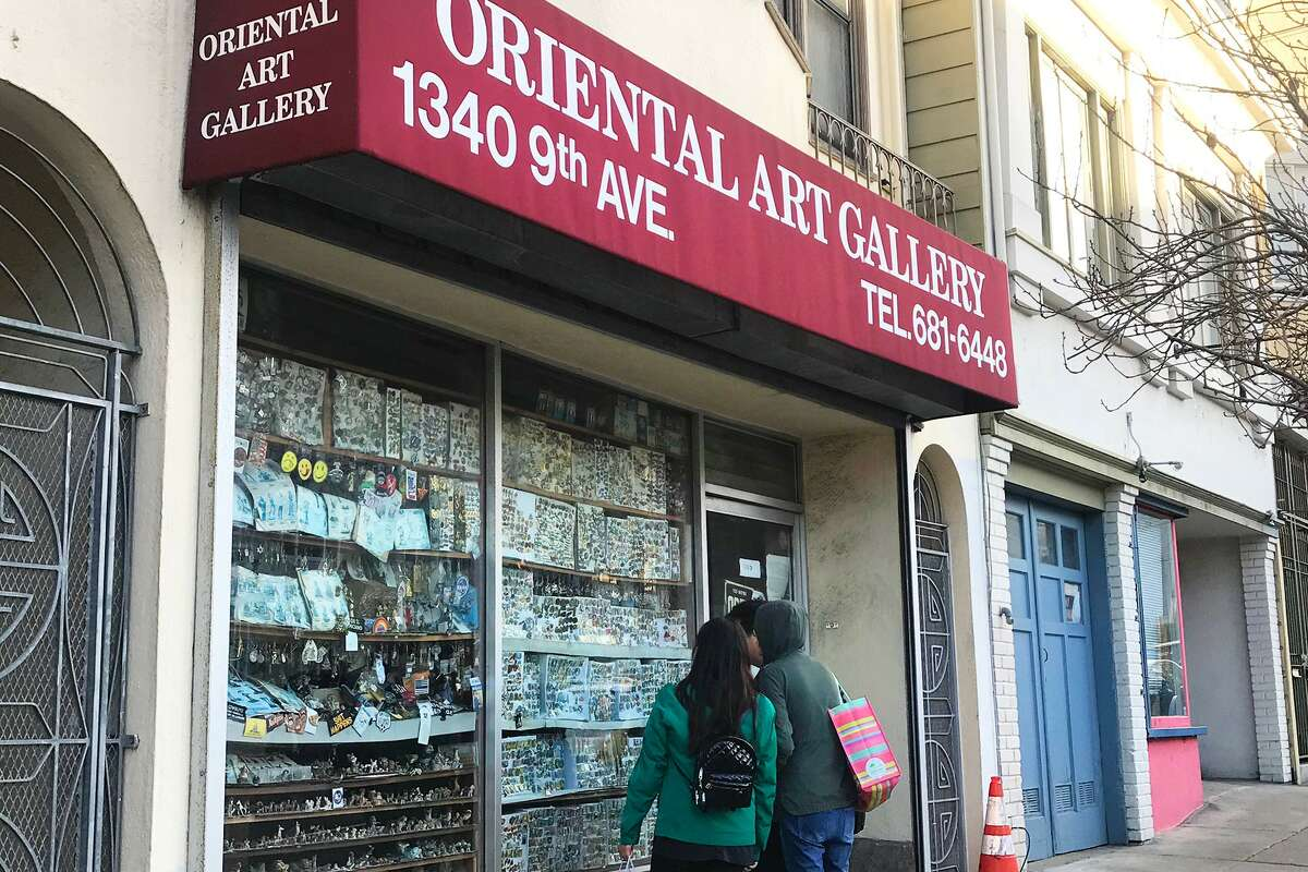Customers peer into the window of the Oriental Art Gallery in the Inner Sunset.