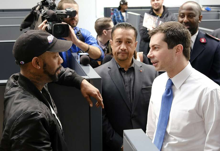 Ex-Mayor Pete Buttigieg (right), at a homeless shelter in Los Angeles on Friday, is short on minority support. Photo: Richard Vogel / Associated Press