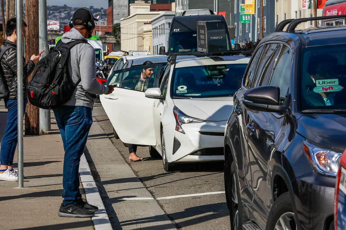 A woman (center) gets into a Lyft car outside the Cal Train station on Townsend Street in San Francisco, California, on Monday, May 20, 2019. Both Uber and Lyft have agreed to a 3.25%-per ride tax in an effort to avoid a tax on their gross receipts. The taxes will generate an estimated $30 million to $35 million for transportation improvements and street-safety upgrades.