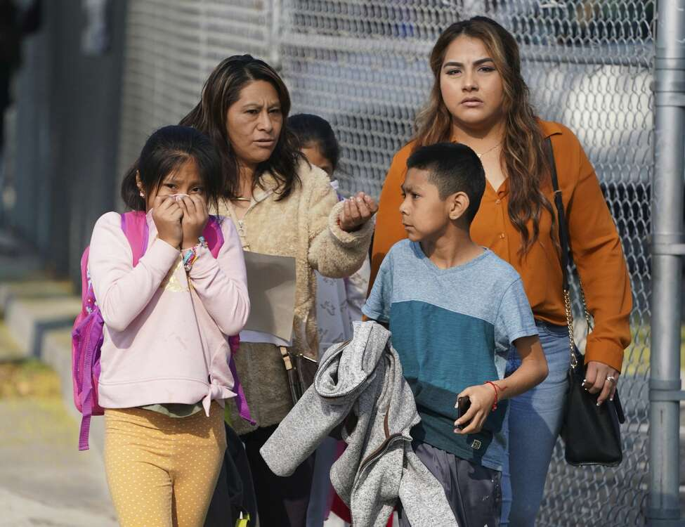 A girl covers her mouth and nose as parents and children leave school after jet fuel was dumped on Park Avenue Elementary School in Cudahy, Calif., Tuesday, Jan. 14, 2020. Jet fuel dumped by an aircraft returning to Los Angeles International Airport fell onto the school playground where children were playing Tuesday, fire officials said. The Los Angeles County Fire Department said firefighters assessed over a dozen children and several adults who complained of minor injuries and none needed to be taken to a hospital. (Scott Varley/The Orange County Register via AP)
