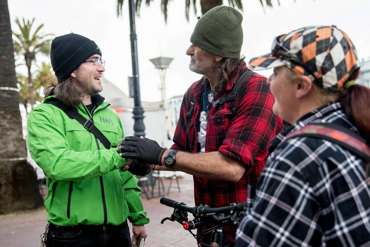 (From left) San Francisco Homeless Outreach Team member Forest Parker shakes hands with James Kelley and Joanna Shober, a homeless couple, after securing them beds in the new Embarcadero Navigation Center in San Francisco, Calif. Tuesday, Jan. 14, 2020.