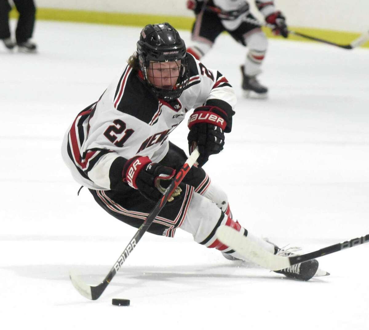 New Canaan's Carter Ellis (21) brings the puck into the offensive zone during the Rams' boys ice hockey game against Northwest Catholic on at the Darien Ice House on Saturday, Jan. 11, 2020.