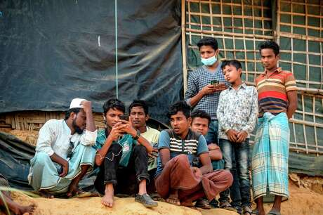 """Rohingya refugees watch on a mobile phone a live feed of Myanmar's State Counsellor Aung San Suu Kyi's appearance at the UN's International Court of Justice in the Hague in the Netherlands, on the second day of her hearing on the Rohingya genocide case, in a refugee camp in Cox's Bazar in southern Bangladesh on Dec. 11, 2019. Texas became the first U.S. state Friday to declare it will not resettle refugees, responding to President Donald Trump's sustained crackdown on all immigration. Governor Greg Abbott told the State Department that Texas has to dedicate its resources """"to those who are already here, including refugees, migrants and the homeless — indeed, all Texans."""""""