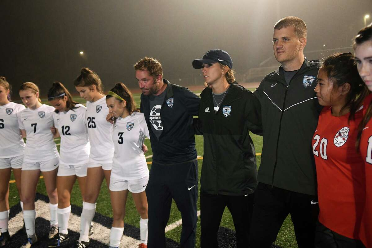 The Kingwood and Atascocita Girls Soccer teams show their support for Head Coach Pres Holcomb, right, before the start of their District 22-6A matchup at Atascocita High School on Jan. 13, 2020.