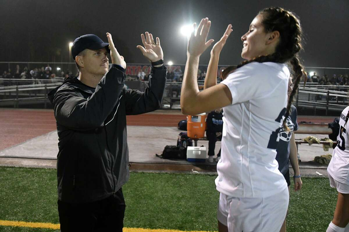 Kingwood Girls Soccer Head Coach Pres Holcomb, left, shares a high-five with senior Emma Ebert during player introductions before the start of their District 22-6A matchup at Atascocita High School on Jan. 13, 2020.
