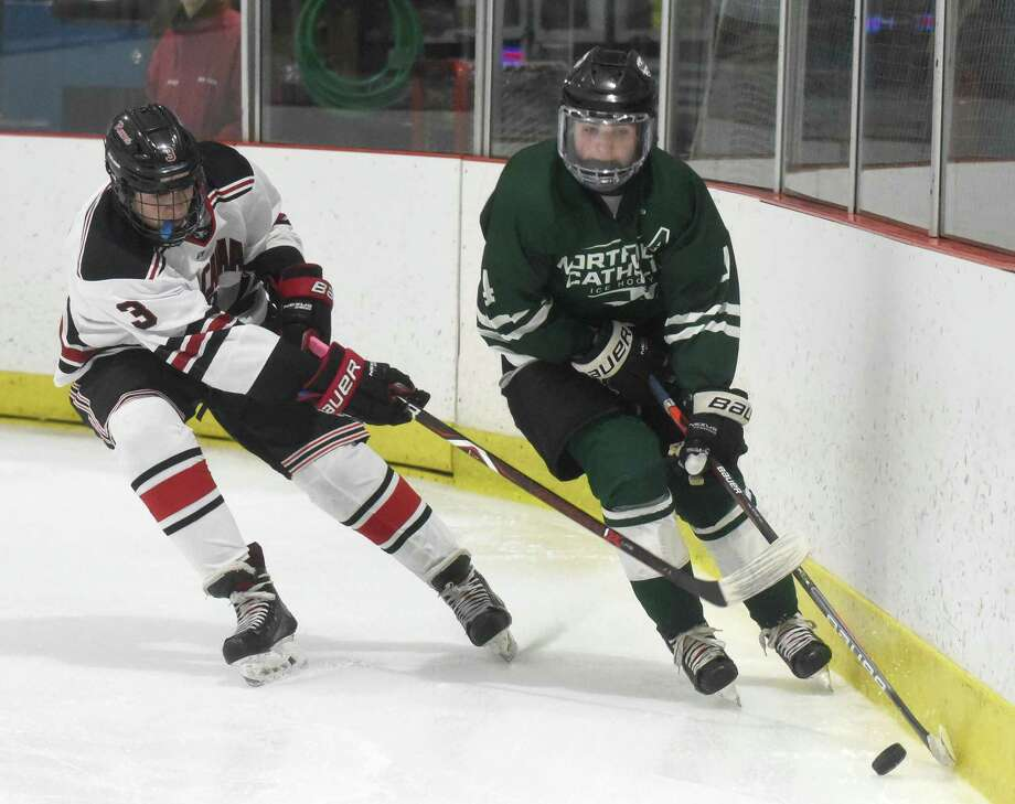 Northwest Catholic's Connor Melanson, right, controls the puck along the boards while being pressured by New Canaan's Alex Sotirhos on Saturday. Photo: Dave Stewart / Hearst Connecticut Media / Hearst Connecticut Media