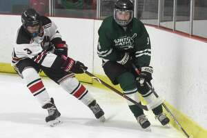 Northwest Catholic's Connor Melanson, right, controls the puck along the boards while being pressured by New Canaan's Alex Sotirhos on Saturday.