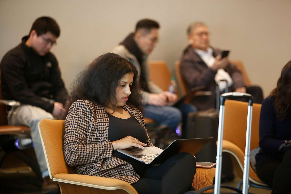 Vidhya Srinivasan of Palo Alto works on a laptop in a filled power holdroom in Terminal B at Norman Y. Mineta San Jose International Airport on Tuesday, January 7, 2020 in San Jose, Calif.