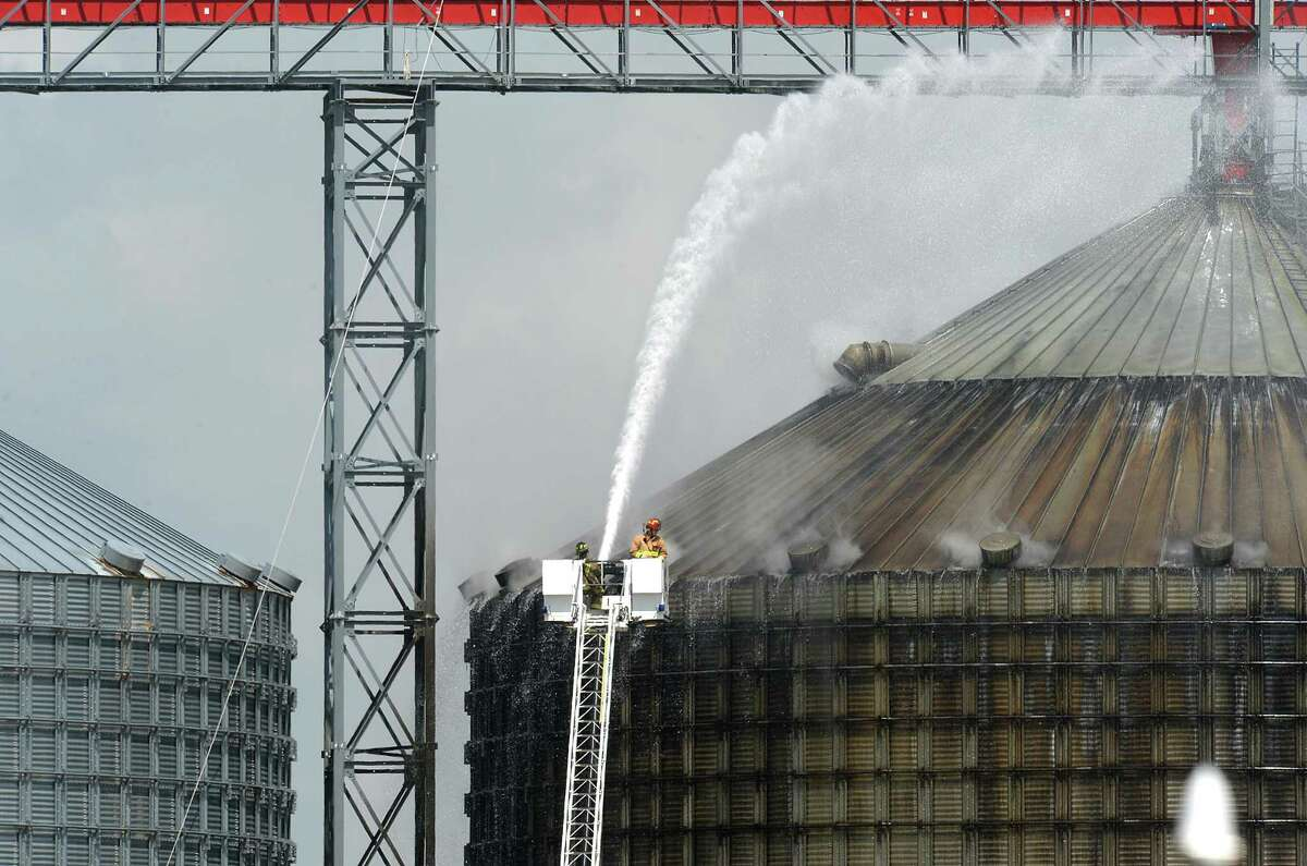 Firefighters spray water on a silo to cool 10,000 tons of smoldering wood pellets at the Port of Port Arthur on Monday. According to city spokeswoman Risa Carpenter, hot spots located by officials Saturday evening ignited early Sunday due to a temperature spike. City firefighters extinguished the flames and began cooling the structure. Port of Port Arthur Director Floyd Gaspard said the fire was started by ?'internal combustion.?