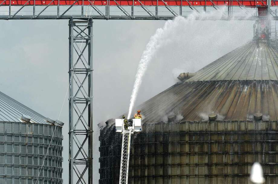Firefighters spray water on a silo to cool 10,000 tons of smoldering wood pellets at the Port of Port Arthur on Monday. According to city spokeswoman Risa Carpenter, hot spots located by officials Saturday evening ignited early Sunday due to a temperature spike. City firefighters extinguished the flames and began cooling the structure. Port of Port Arthur Director Floyd Gaspard said the fire was started by Òinternal combustion.Ó The pellets originated from the German Pellets facility in Woodville, where a fire occurred in April of 2014.  On Feb. 27, a conveyor belt loading a ship at the Port of Port Arthur with several tons of wood pellets caught fire, setting the wood ablaze and sending a colossal cloud of black smoke into the air. Photo taken Monday, April 17, 2017 Guiseppe Barranco/The Enterprise Photo: Guiseppe Barranco, Photo Editor / Guiseppe Barranco/The Enterprise