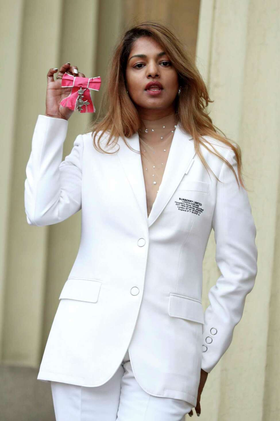 Rapper and singer MIA, real name Mathangi Arulpragasam, poses with her MBE award following an investiture ceremony at Buckingham Palace in London, Tuesday Jan, 14, 2020. The British Empire award is presented in royal recognition of contributions to the arts, sciences, and charitable works. (Yui Mok/PA via AP)