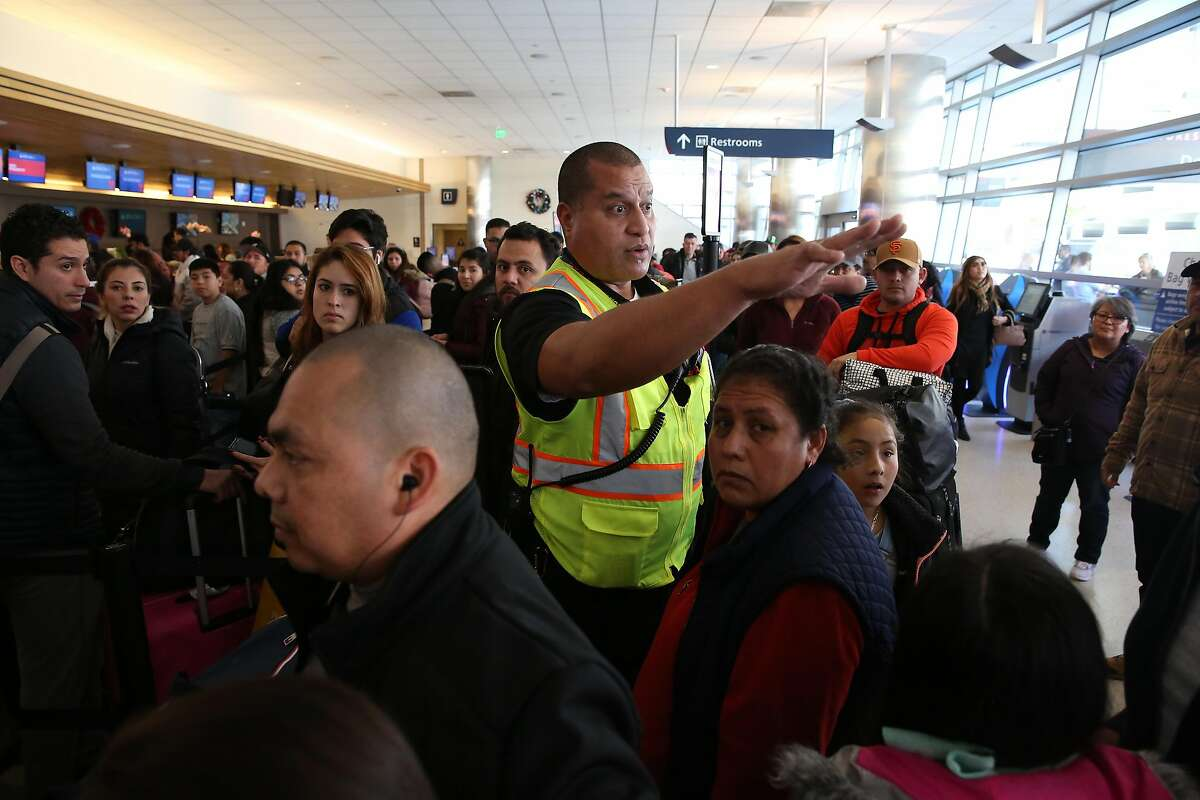 Michael Aliki, airport operations, helps to organize the crowd of passengers as he works in the ticketing area of Terminal A at Norman Y. Mineta San Jose International Airport on Tuesday, January 7, 2020 in San Jose, Calif.