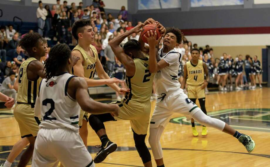 Conroe player Michael Phoenix (2) and College Park guard Ty Buckmon (11) fight for a rebound in a District 15-6A boys basketball game at College Park High School in The Woodlands. Photo: Gustavo Huerta, Houston Chronicle / Staff Photographer / Houston Chronicle