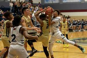 Conroe player Michael Phoenix (2) and College Park guard Ty Buckmon (11) fight for a rebound in a District 15-6A boys basketball game at College Park High School in The Woodlands.