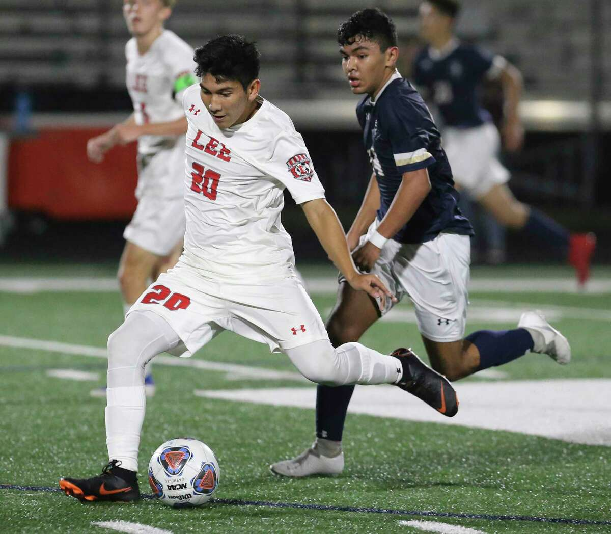 LEE's Efrain Cortes (20) passes the ball against Central Catholic's Bryan Jimenez (14) in boys soccer at Central Catholic on Tuesday, Jan. 14, 2020. LEE defeated Central Catholic, 1-0, to take the win between the two top rated high school teams.