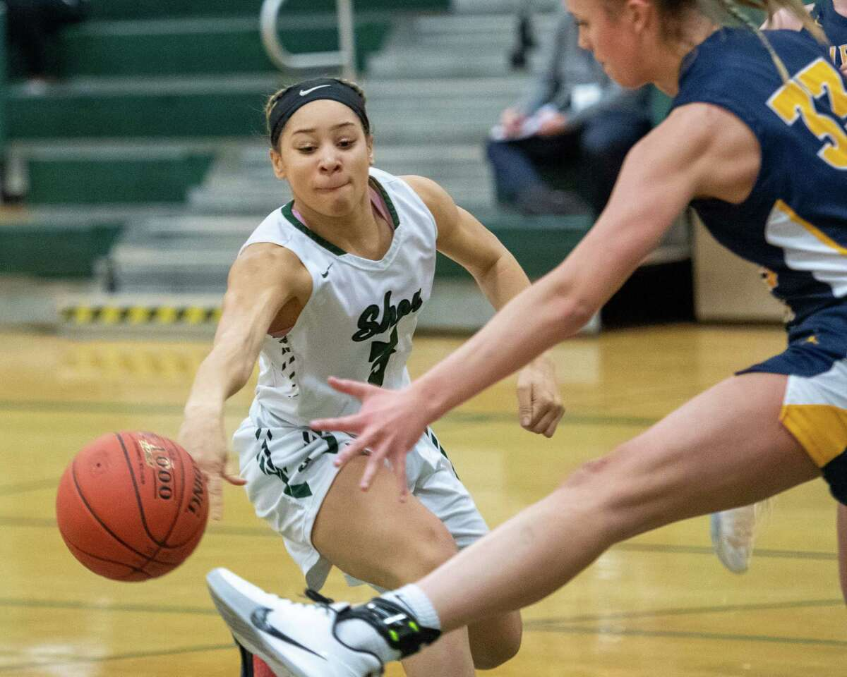 Shenendehowa senior Simone Walker passes the ball in front of the outstretched hand and foot of Averill Park sophomore Amelia Wood during a Suburban Council game at Shenendehowa High School on Tuesday, Jan. 14, 2019 (Jim Franco/Special to the Times Union.)